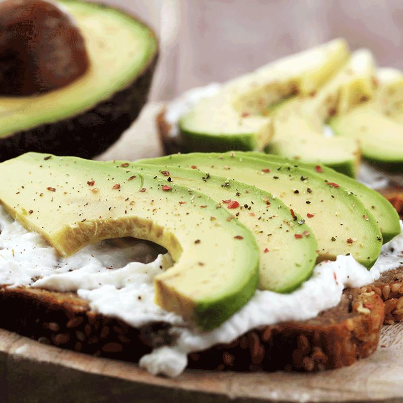 Een volkoren boterham met cottage cheese en avocado, lekker en gezond!