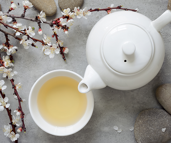 Witte thee in een kopje met een theekan