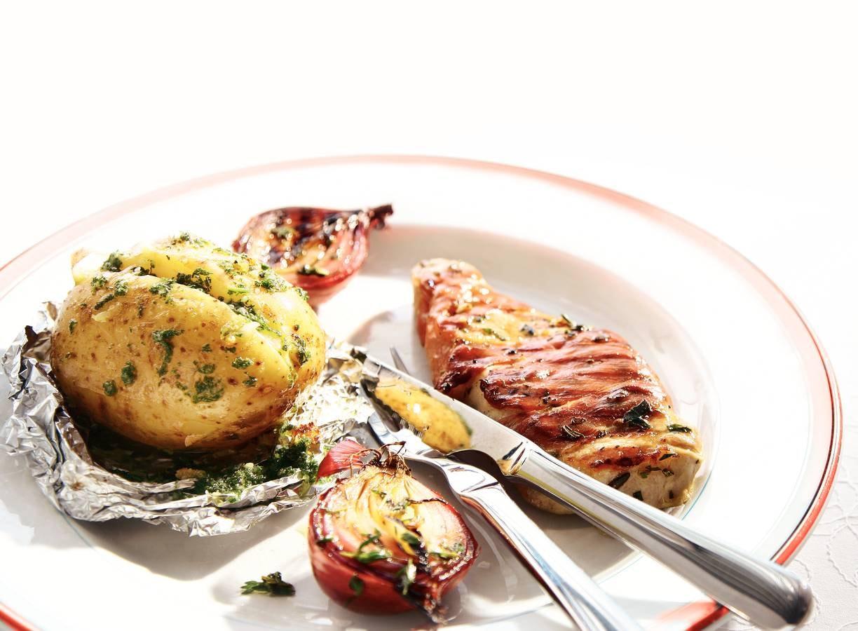 In ham verpakte varkenslapjes met aardappel en rode ui