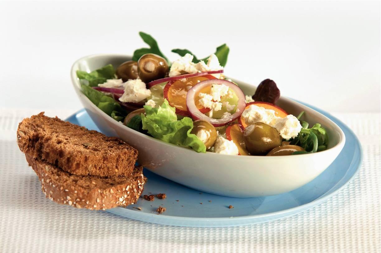 Gemengde salade met witte kaas, olijven en nectarine