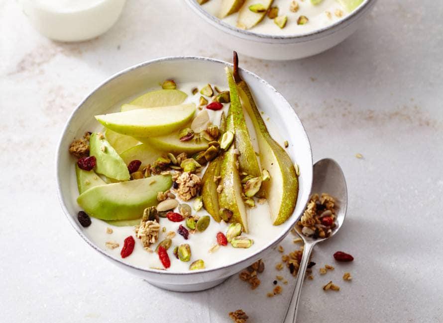 Sojayoghurt ontbijt met pistachenoten, appel, peer, limoen, avocado en granola.