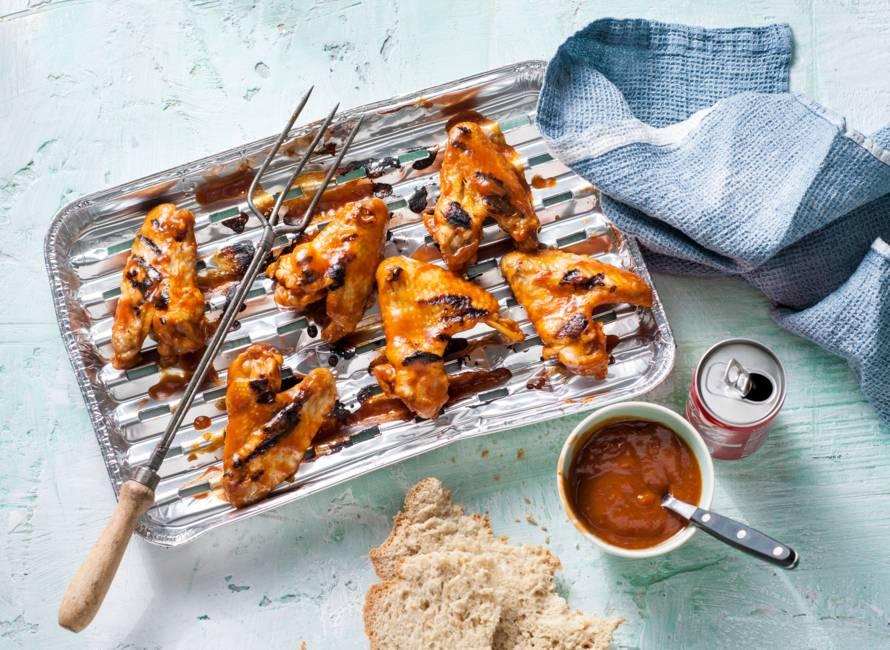 Sticky kip en cola van een wegwerpbarbecue