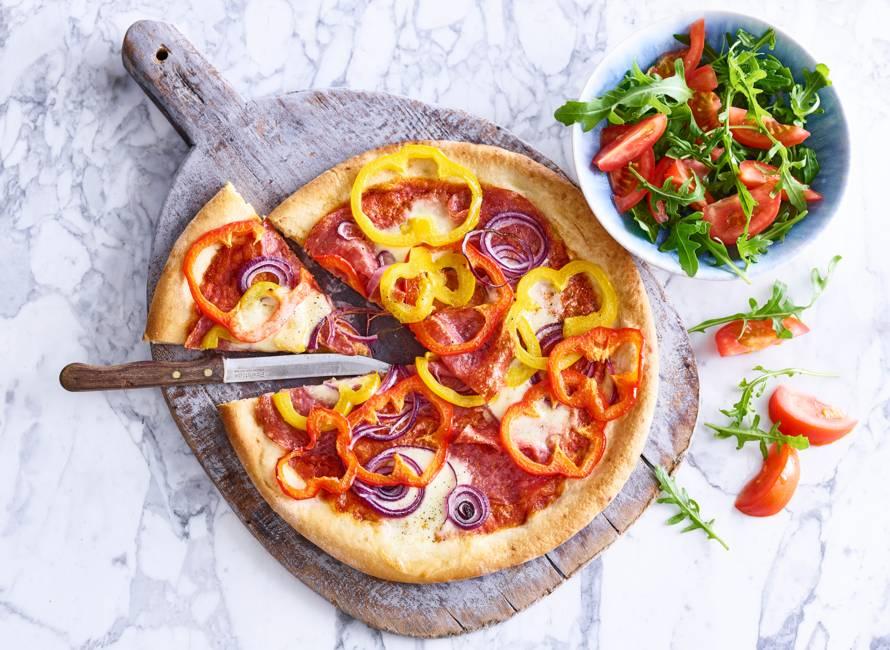 Salamipizza met mozzarella en tomatensalade