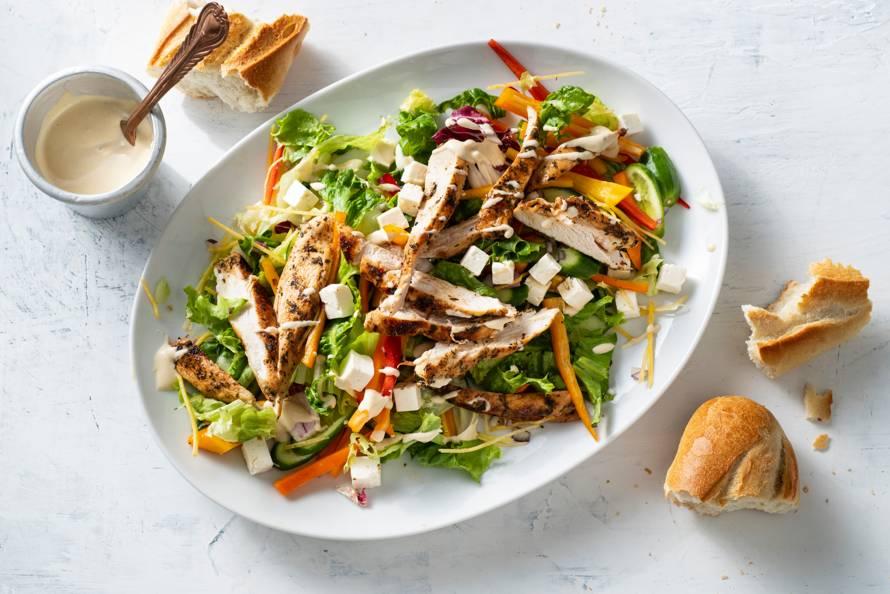 Mediterrane salade met kruidige kip en hummusdressing