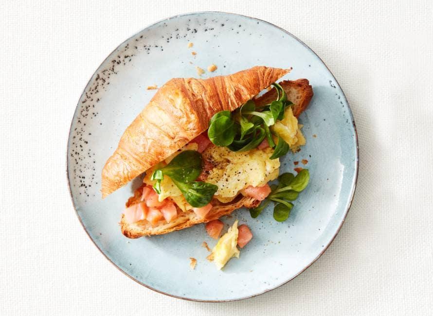 Croissant gevuld met roerei, gerookte zalm en veldsla