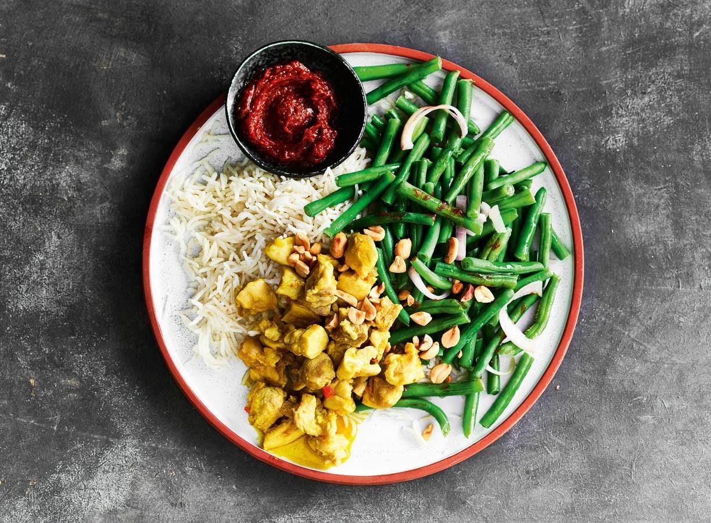 Pittige kipdij met rijst, sperziebonen en knapperige pinda's