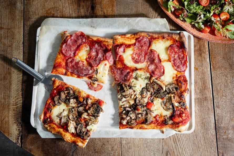 Pizza met mozzarella, paddenstoelen en salami