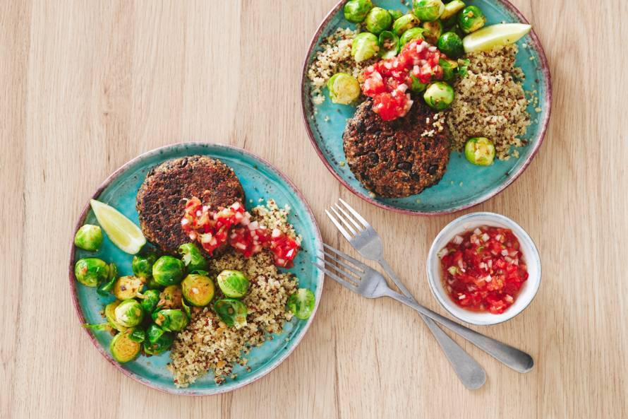 Zwarte-bonenburgers met pittige tomatensaus, quinoa en spruitjes