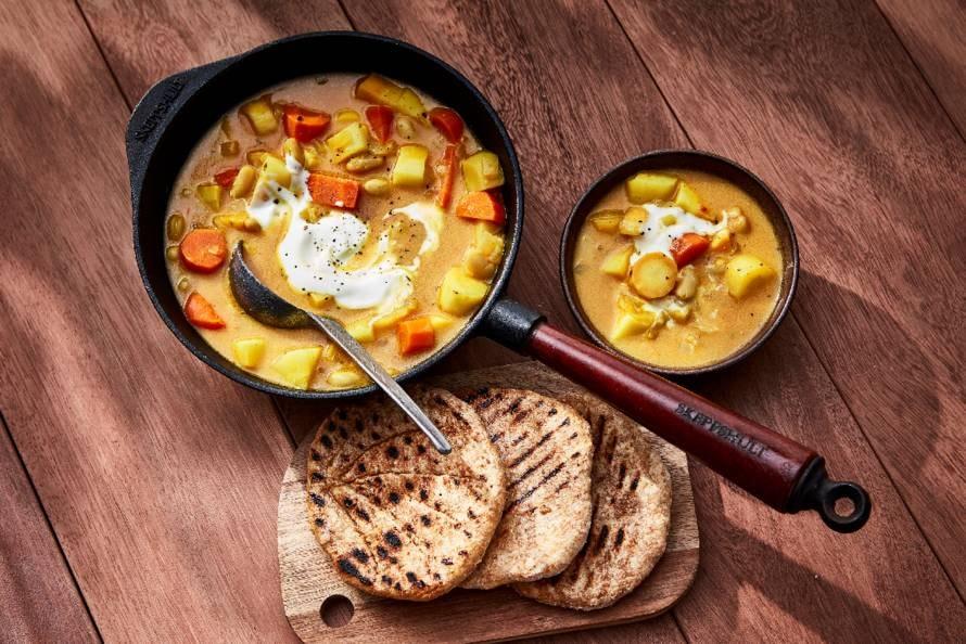 Vegan curry van gestoofde groenten met naan