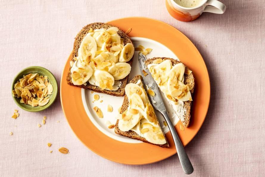 Volkorenbrood met zuivelspread, banaan en amandelschaafsel